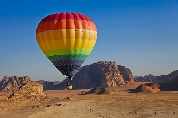 A family flying over Wadi Rum National Reserve, which is also known as The Valley of the Moon, in a colourful hot air balloon.